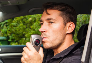 a drunk driver using a breathalyzer